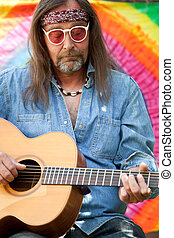 Bearded middle-aged hippie man playing the guitar - Bearded...