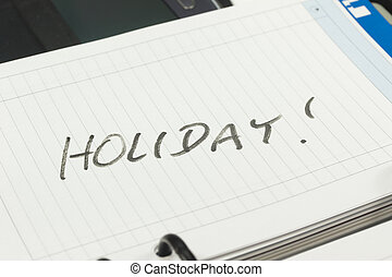 Open page of paper managers diary with an inscription HOLIDAY