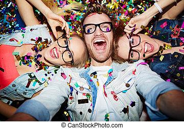 Selfie in nightclub - Cheerful friends lying on the floor in...