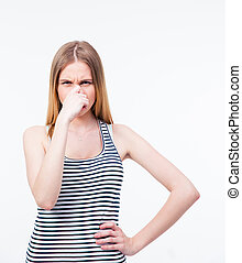 Young woman covering her nose with hand over gray background...