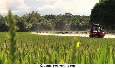 farmer spray field - Farmer with tractor spray fertilize...