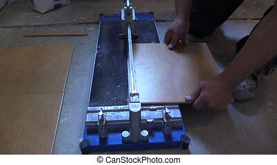 tile cutter builder work - worker hand using tile cutter at...