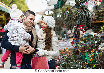 Smiling family in Christmas fair - Smiling parents and child...