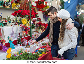 Couple buying Christmas flower at market - Smiling couple...