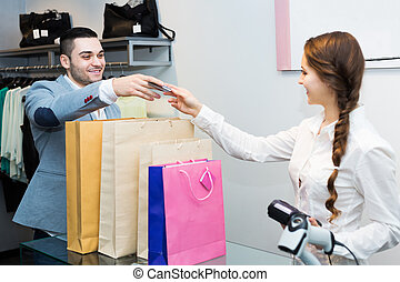 Store clerk serving purchaser - Smiling store clerk serving...