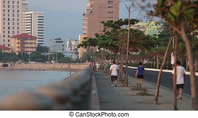 view of city embankment and beach with tourists at dawn