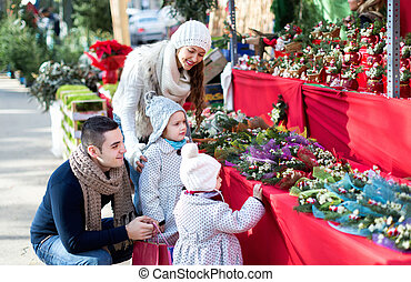 Family of four at Christmas market - Smiling married couple...