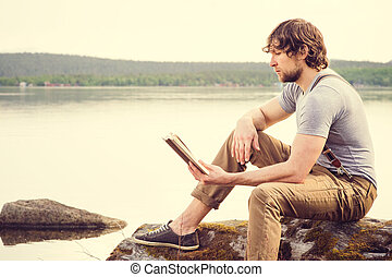 Young Man reading book outdoor with scandinavian lake on...