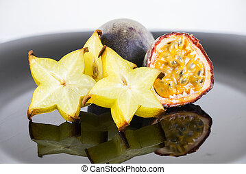 Tropical fruits over black plate