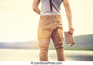 Young Man standing with book outdoor with scandinavian lake...