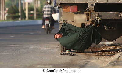 man sleeps in hammock under lorry on road with cars