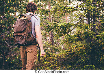 Young Man hiking in forest with backpack Travel Lifestyle...
