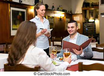 Family couple in restaurant - Young family couple eating out...
