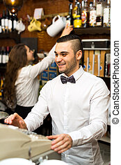 Bartender working at checkout counter - Male bartender...