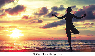 Yoga woman meditating on the beach during sunset sunset...