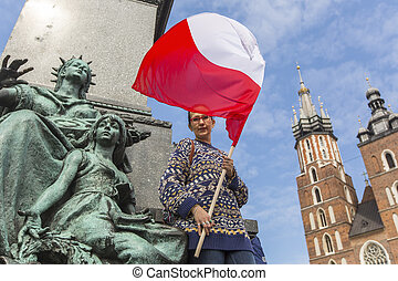 Woman with the Polish flag in the main square of Krakow,...