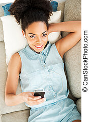 Relaxing with her favorite music. Top view of attractive young African woman in headphones listening to the music and smiling while lying on the couch at home