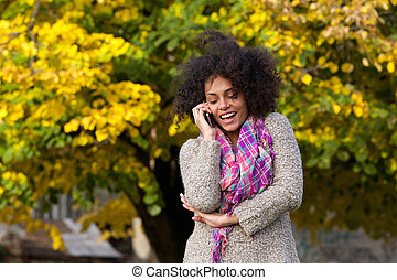 Cheerful young woman talking on mobile phone - Portrait of a...