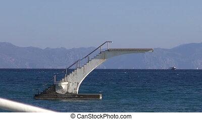 empty diving platform on Aegean sea and resort beach in...