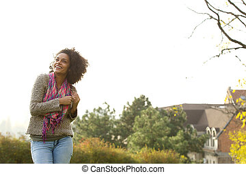 Cheerful young woman laughing outside