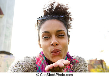 Attractive young woman blowing a kiss