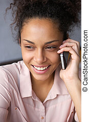 Smiling black woman talking on cell phone - Close up...