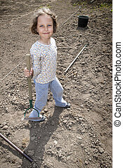 During planting - Girl standing with hoe during preparation...