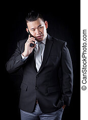 portrait of asian business man talking mobile phone against...