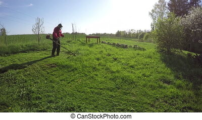 farmer mowing grass with trimmer - farmer cut mowing grass...