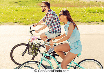 Having great time together Cheerful young couple riding...