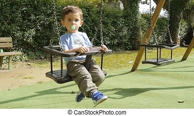 Young Boy Playing On A Swing - child having fun in...