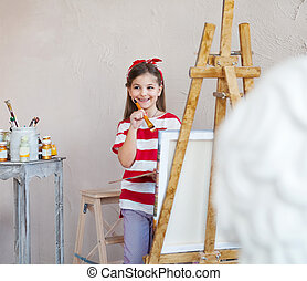 Little artist girl holding a paintbrush and looking over a...