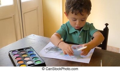 kid having fun with watercolors - portrait of little boy...