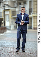 Stylish man in a blue suit with a butterfly tie on the...