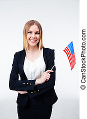 Smiling young businesswoman holding US flag isolated on a...