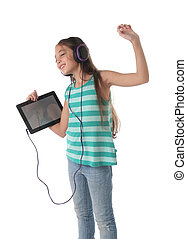 Beautiful pre-teen girl dancing with a tablet and...