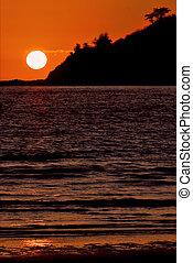 sun near a mountain in the ocean - sunset near a mountain in...
