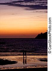 reflex in the beach in the sun - sunset near a mountain in...