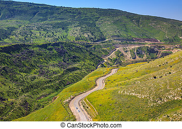 Serpentine road winds through the green hills Israels border...