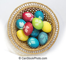 Easter colored eggs in a wicker vase on a white background