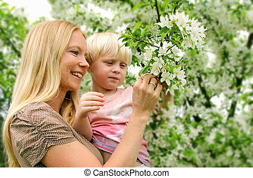 Mother and Young Child Looking at Flowering Crabapple Tree -...
