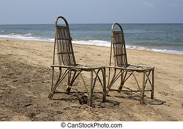 Two wattled chairs stand on a beach, wait for people against...