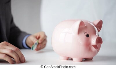close up of man putting money into piggy bank - people,...