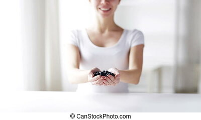 close up of young woman showing blueberries - healthy...
