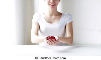 close up of young woman showing raspberries - healthy...