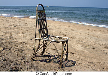 The lonely wattled chair costs on a beach, against the sea...