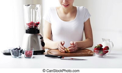 smiling woman with blender making fruit shake - healthy...