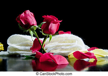 two red roses together with red petals on a black background...