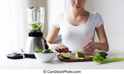 smiling woman with blender and green vegetables - healthy...
