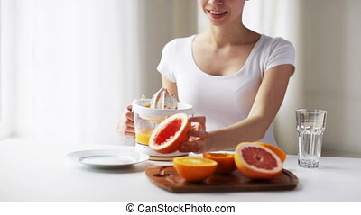 woman with squeezer pouring orange juice to glass - healthy...